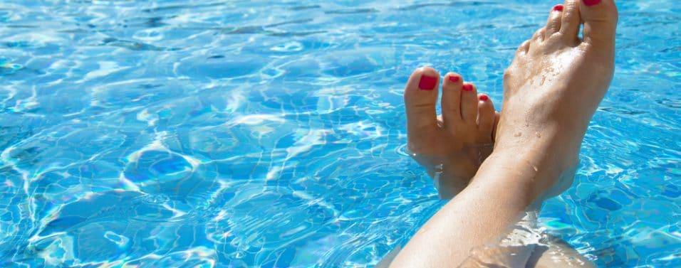 Feet relaxing by pool