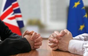 UK and Europe flags with hands on a desk