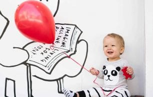 Baby holding balloon laughing