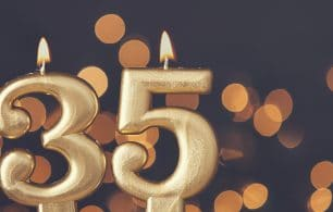 Gold number 35 celebration candle against blurred light background