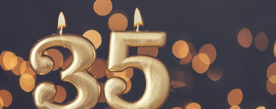 Gold number 35 celebration candle against blurred light background