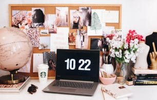 desk with macbook and vision board