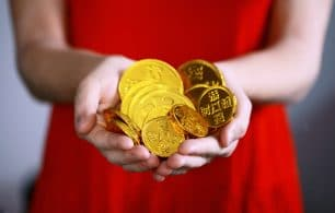 Girl holding gold coins red dress