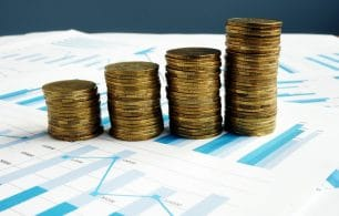 Profit increase. Stacks of coins and financial report.
