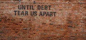 Until debt tear us apart painted on brick wall