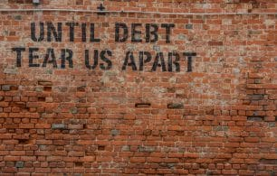Until debt tear us apart painted on brick wall