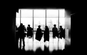 Black and white photo of people at boardroom table
