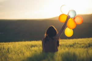 woman holding balloons in a field