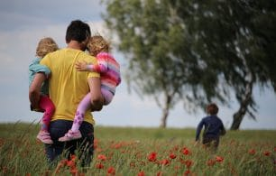 Dad holding two kids through poppy field