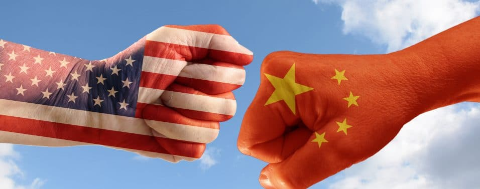 Trade conflict, fists with the flags of USA and China against each other, blue sky with clouds in the background