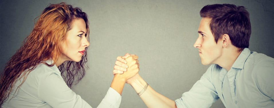 woman and man arm wrestling