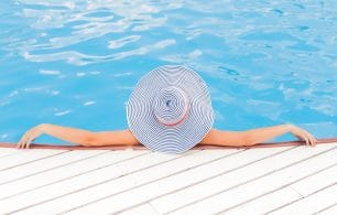 Woman in pool with large sunhat