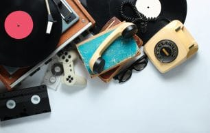 Retro 80s pop culture objects on white background. Copy space. Rotary phone, vinyl player, old books, audio, video tapes, 3d glasses, gamepad.
