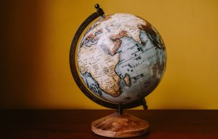globe on desk with yellow background