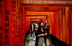 woman with mask walking through torii gate japan
