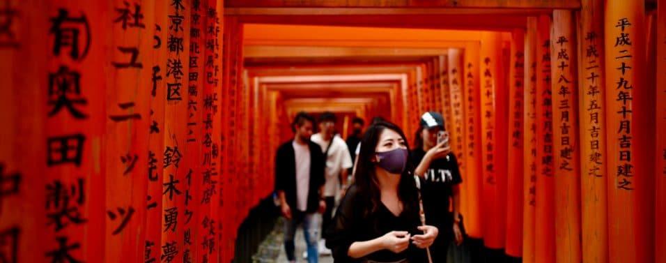 woman with mask walking through torii gate japan