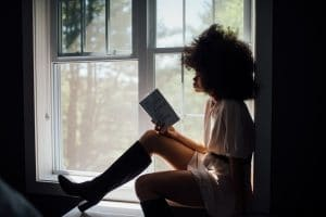 women reading book next to window