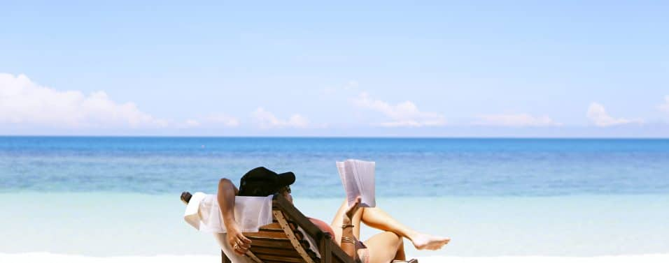 woman reading a book on beach